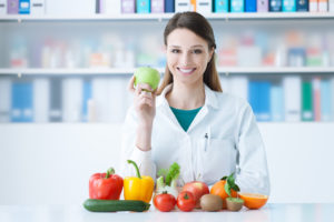 Medical person holding a green apple and showing healthy vegetables and fruits, healthcare and diet concept